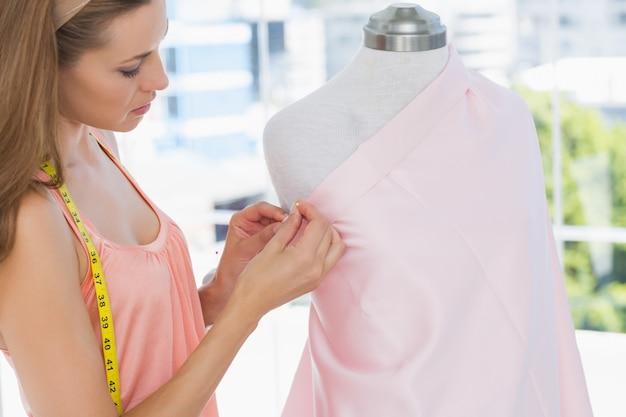 Schöner weiblicher modedesigner, der an rosa gewebe arbeitet