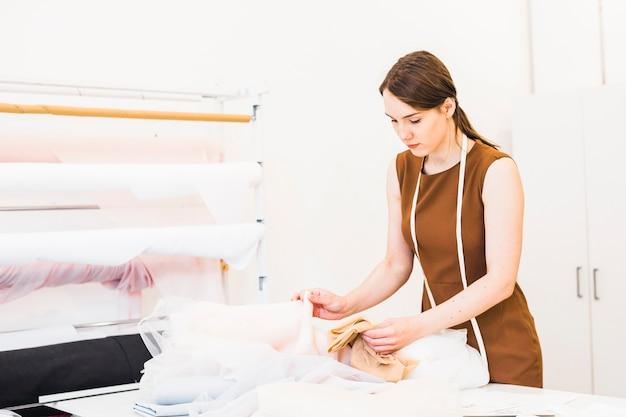 Schöner weiblicher modedesigner, der gewebe im studio wählt