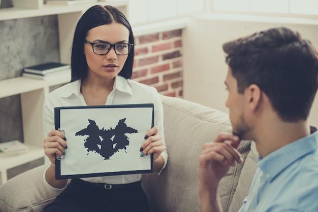 Schöner weiblicher psychologe führt den tintenflecktest durch
