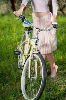 Schöner weiblicher radfahrer mit retro- garten des fahrrades im frühjahr