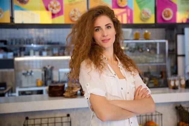 Schöner weiblicher rothaariger barista, der kamera betrachtet und lächelt