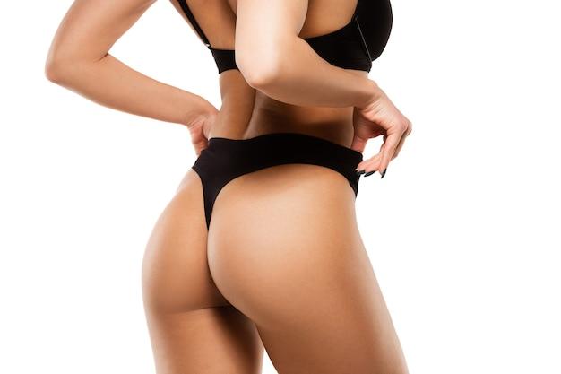 Schöner weiblicher rücken und gesäß isoliert auf weißer wand. beauty, kosmetik, spa, depilation, behandlungs- und fitnesskonzept. fit und sportlich, sinnlicher body mit gepflegter haut in unterwäsche.