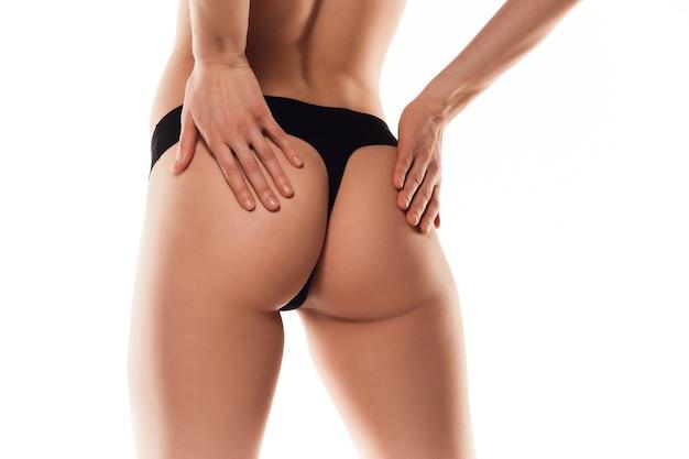 Schöner weiblicher rücken und hintern lokalisiert auf weißer wand. beauty, kosmetik, spa, depilation, behandlungs- und fitnesskonzept. fit und sportlich, sinnlicher body mit gepflegter haut in unterwäsche.