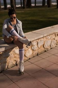 Schöner weiblicher schlittschuhläufer, der die spitze des rollschuhs bindet