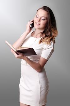 Schöner weiblicher sekretär, der im büro an ihrem arbeitsplatz, den planer halten steht und lesen zeitplan für den tag, seitenansichtporträt