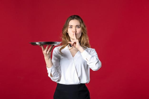 Schöner weiblicher server-schmetterling am hals und hält tablett, das eine stille-geste auf rotem hintergrund macht