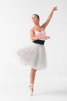 Schöner weiblicher tänzer im eleganten weißen ballettröckchen gegen weißen hintergrund