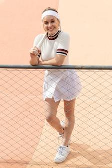 Schöner weiblicher tennisspieler, der kamera betrachtet
