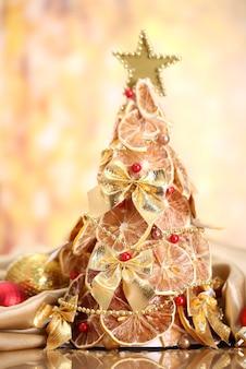 Schöner weihnachtsbaum aus trockenen zitronen mit dekor, auf gelbem hintergrund