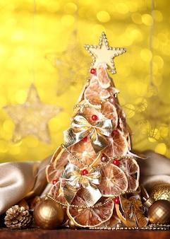 Schöner weihnachtsbaum der trockenen zitronen mit dekor, auf gelb