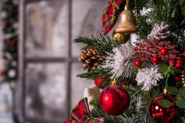 Schöner weihnachtsbaum in einem wohnzimmer. schöner luxusfeiertag verzierte raum mit weihnachtsbaum, kamin und lehnsessel mit decke. gemütliche winterszene. weißer innenraum mit lichtern.