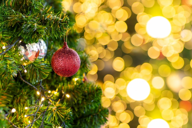 Schöner weihnachtsbaum mit dekor gegen unscharfes bokeh beleuchtet im hintergrund.