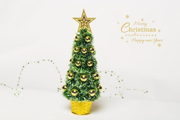 Schöner weihnachtsbaum mit goldkugeln und weißem hintergrund der girlandenlichter