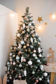Schöner weihnachtsbaum mit rosa und blauen spielzeugen im kinderzimmer