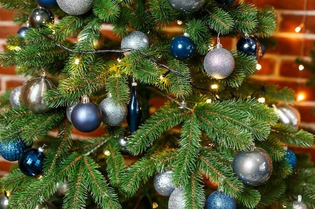 Schöner weihnachtsbaum verziert mit blauen und silbernen spielsachen. silvester ist bald. dekorationen für den weihnachtstag