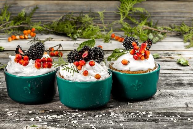Schöner weihnachtscupcake mit sahne und beeren auf holzwandzimtkegeln