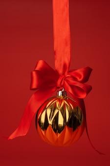 Schöner weihnachtsflitter, der am roten satinband gegen rot hängt