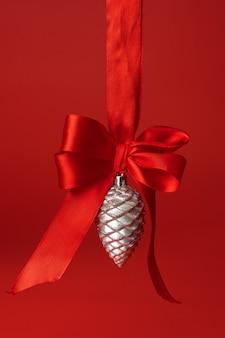 Schöner weihnachtsflitter, der am roten satinband gegen roten hintergrund hängt