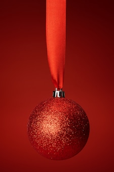 Schöner weihnachtsflitter, der am roten satinband hängt
