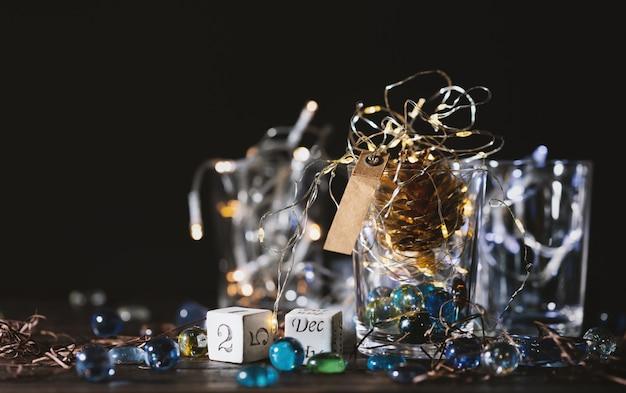 Schöner weihnachtshintergrund mit blockkalender und glühenden weihnachtslichtern in einem glasgefäß.