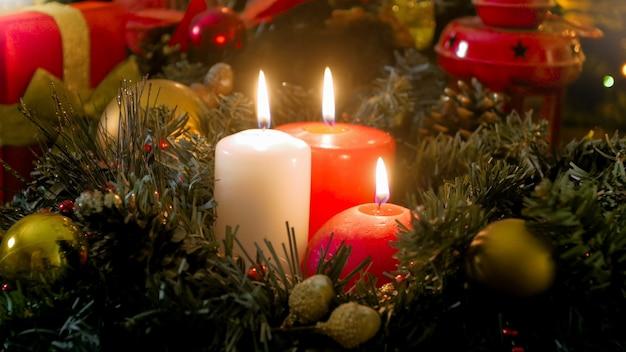 Schöner weihnachtshintergrund mit glühenden kerzen, geschenkboxen und kranz auf gedecktem tisch