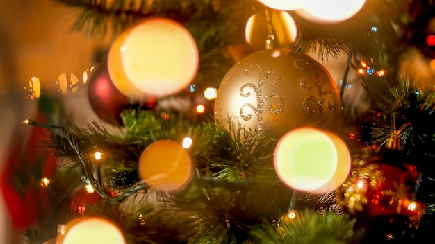 Schöner weihnachtshintergrund mit goldenem christbaumkugeln und hellem girlande bokeh