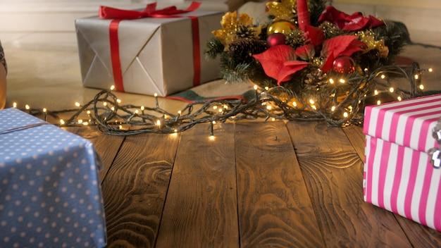 Schöner weihnachtshintergrund mit lichtern, geschenken und weihnachtsbaum auf holzflor. kopieren sie platz für ihren text oder design