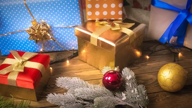 Schöner weihnachtshintergrund mit vielen kugeln und geschenken in kisten auf holzuntergrund