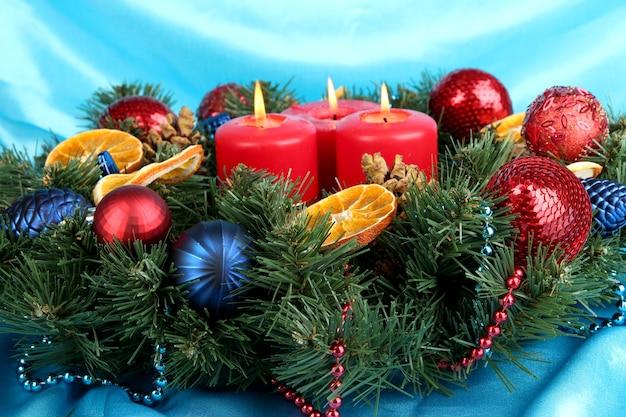 Schöner weihnachtskranz auf blauer stoffoberfläche