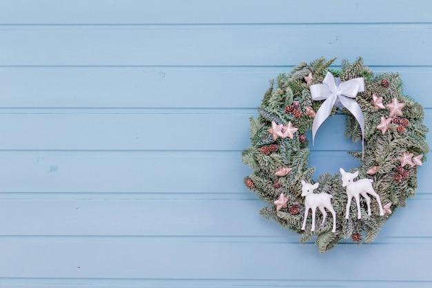 Schöner weihnachtskranz auf der blauen holzwand
