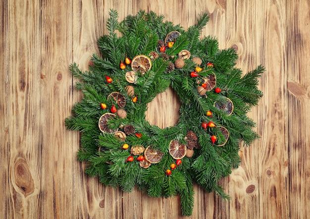 Schöner weihnachtskranz auf holzwand