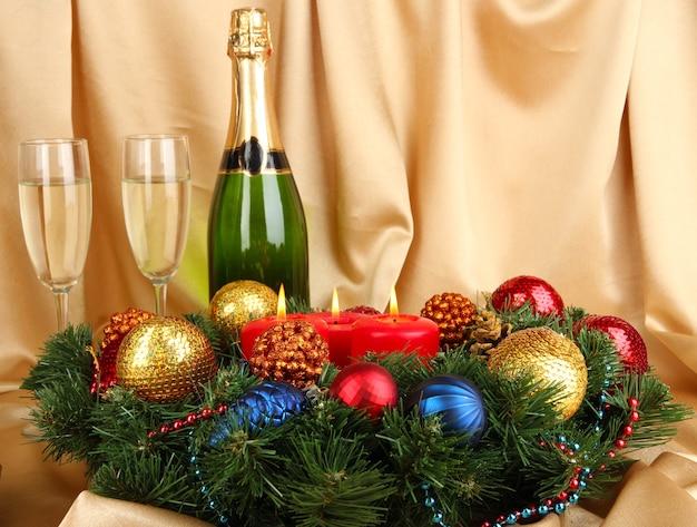 Schöner weihnachtskranz in komposition mit champagner auf goldener stoffoberfläche Premium Fotos