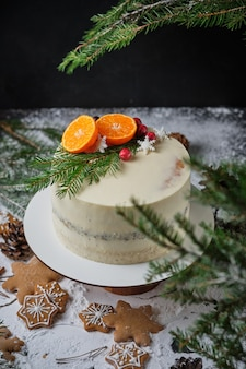 Schöner weihnachtskuchen für weihnachten dekoriert mit mandarinen frischen beeren schneeflocken