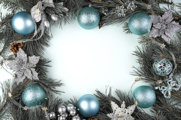 Schöner weihnachtsrahmen mit blauen und silbernen spielzeugen auf einer blauen oberfläche