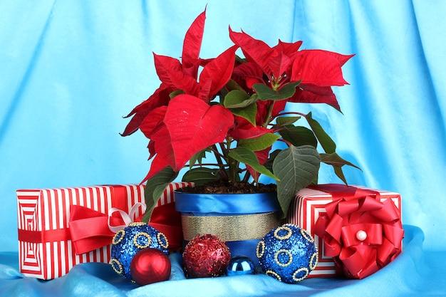 Schöner weihnachtsstern mit weihnachtskugeln und geschenken auf blauem stoffhintergrund