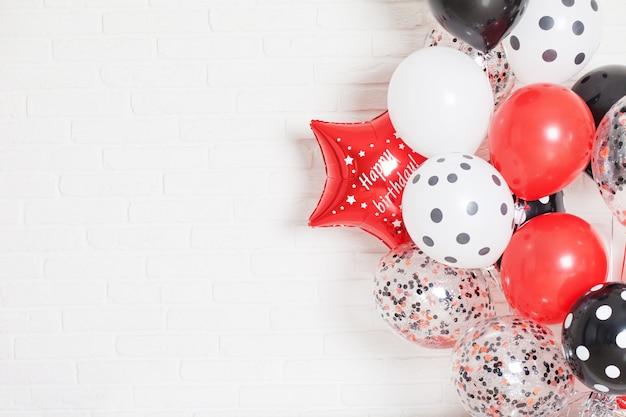 Schöner weißer backsteinmauerhintergrund mit roten, weißen und schwarzen luftballons. konzept von glück und freude. speicherplatz kopieren