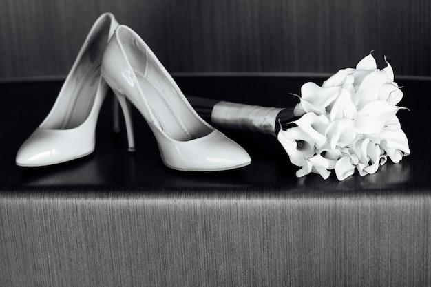 Schöner weißer hochzeitsblumenstrauß von lilien liegt nahe bei den schuhen der braut