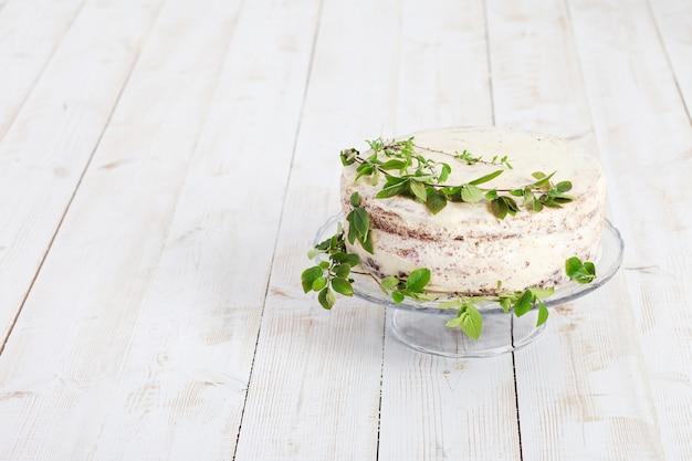 Schöner weißer kuchen, der durch grüne zweige verziert wird. hochzeits- oder geburtstagsfeier. speicherplatz kopieren
