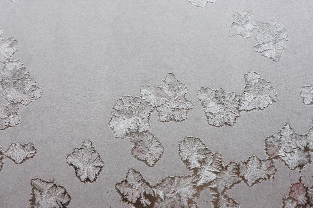 Schöner winterhintergrund, frost am fenster, natürliche textur auf glas mit einem gefrorenen muster.