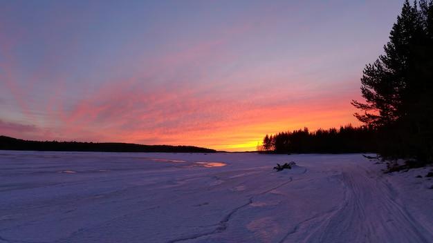 Schöner wintersonnenuntergang in karelien über gefrorenem weißem meer