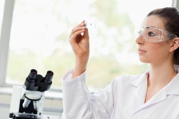 Schöner wissenschaftsstudent, der einen objektträger betrachtet