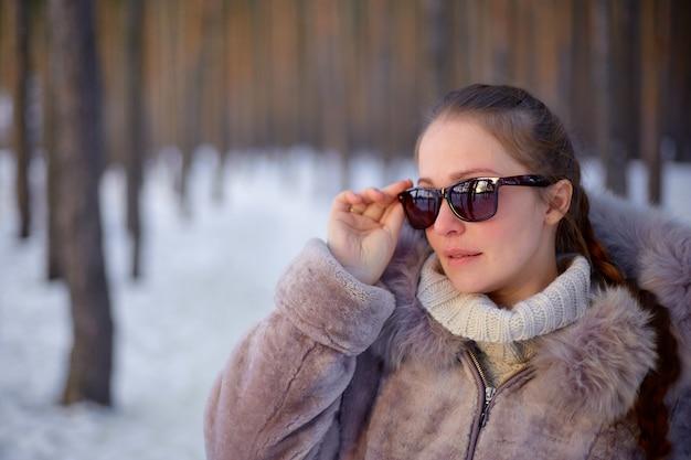 Schöner womanin winterwald, der einen pelzmantel und eine sonnenbrille trägt.