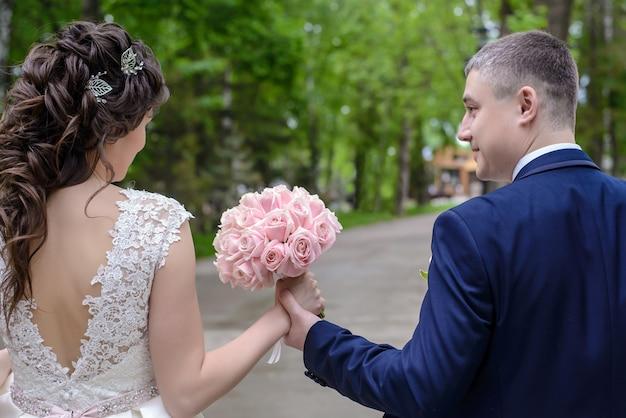 Schöner zarter brautstrauß aus rosa rosen in den händen von braut und bräutigam, die im sommer im park spazieren gehen