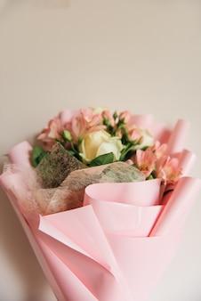 Schöner zarter rosa blumenstrauß aus weißen rosen und eustoma in einer schönen verpackung