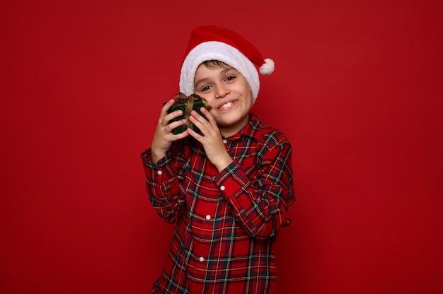 Schöner zarter süßer kleiner junge, entzückendes kind in weihnachtsmütze und kariertem hemd umarmt sanft sein weihnachtsgeschenk in grünem geschenkpapier mit goldener schleife, einzeln auf rotem hintergrund mit kopierraum