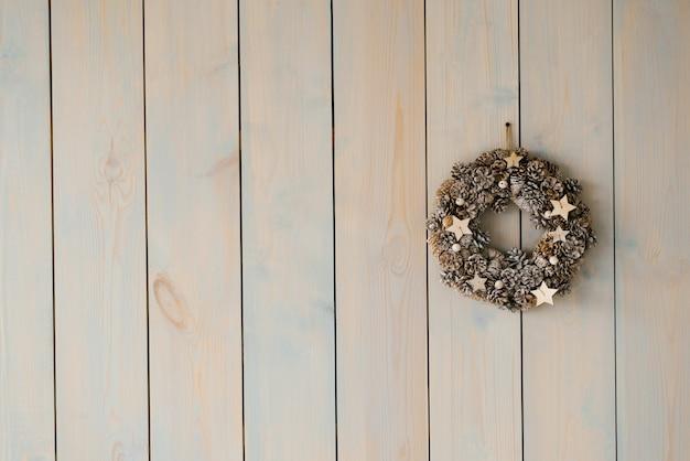 Schöner zarter weihnachtskranz an der grauen wand.