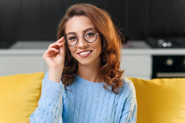 Schönes 25-jähriges mädchen im weichen blauen pullover, der brille trägt und die kamera mit niedlichem perfektem lächeln auf dem hintergrund der stilvollen küche betrachtet.
