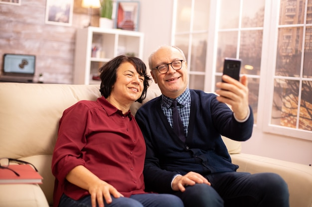 Schönes älteres ehepaar, das ein selfie macht, während es auf der couch im wohnzimmer sitzt