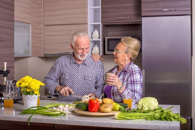 Schönes älteres ehepaar, das in der küche miteinander kocht