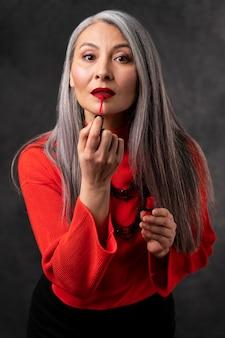 Schönes älteres frauenporträt, das lippenstift anwendet